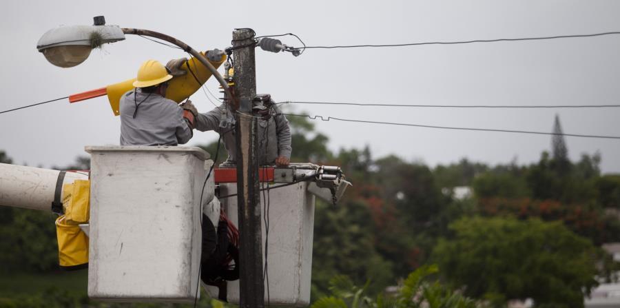 Varios trabajadores trabajan en un poste de luz. (GFR Media) (horizontal-x3)