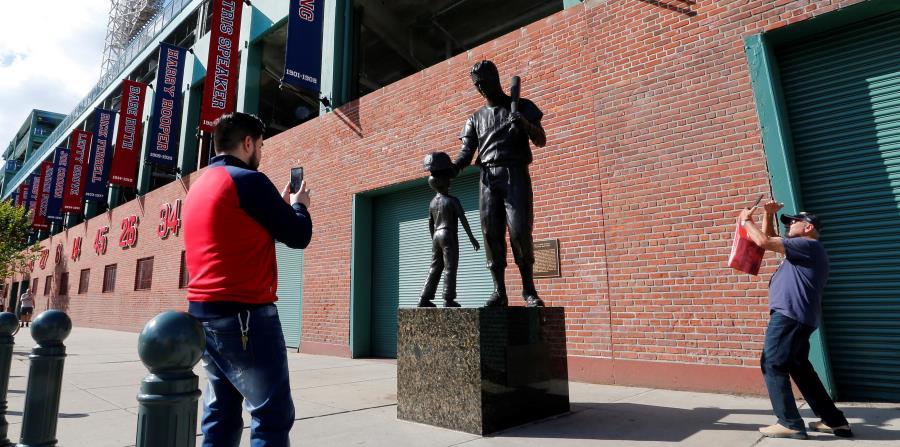 Dos fanáticos de los Medias Rojas se detienen en los alrededores del Fenway Park para retratar la estatua del legendario Ted Williams, cuando la novena local abrirá mañana la Serie de Campeonato de la Liga Americana ante Houston. (AP / Elise Amendola) (horizontal-x3)