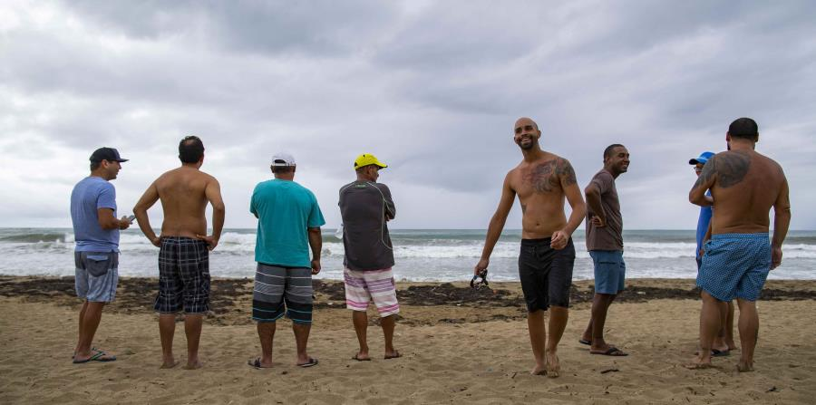 """Algunos residentes llegaron hasta la costa de la playa Pozuelo para ver a los surfers. (Ramón """"Tonito"""" Zayas)"""