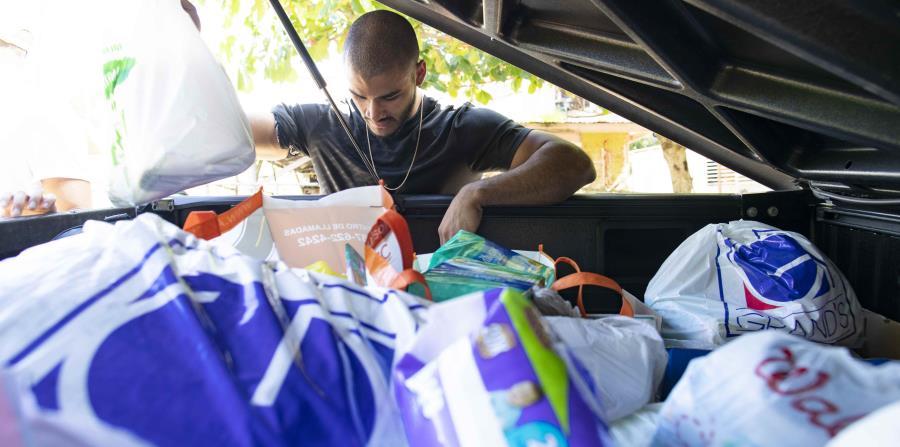 El bayamonés José Díaz saca suministros de emergencia de la parte trasera de una camioneta.