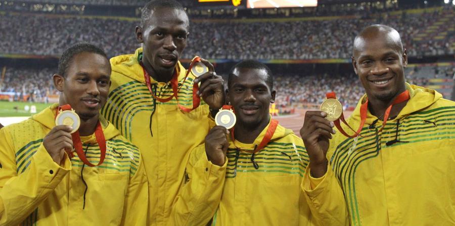 El equipo de Jamaica en relevos 4x100 de hombres, de izquierda a derecha, Michael Fraser, Usain Bolt, Nesta Carter y Asafa Powell posan con sus medallas de oro en las competencias de atletismo en el Estadio Nacional de los Juegos Olímpicos de Beijing 2008 (horizontal-x3)