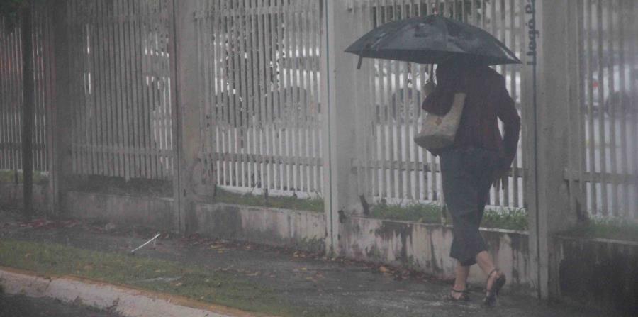 Una mujer camina por una carretera en Hato Rey con sombrilla en mano para evitar mojarse con la lluvia. (GFR Media) (horizontal-x3)