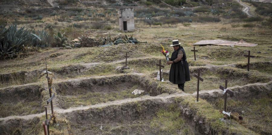 En esta imagen del 16 de agosto, Lidia Flores coloca flores en La Hoyada, el lugar en el que cree que su esposo, Felipe Huaman Palomino, desapareció en Huamanga, Perú. (AP)