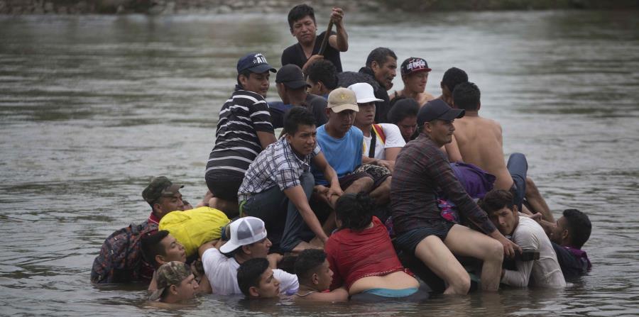 Un grupo de migrantes centroamericanos cruzaba ayer el río Suchiate en una balsa hecha de gomas y tablas, en la frontera entre Guatemala y México. (AP / Moises Castillo)