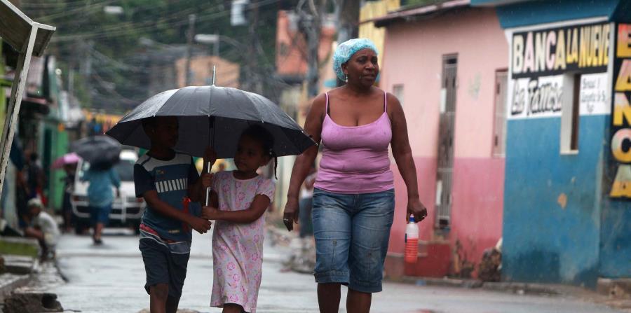 Una mujer y dos niños caminan hoy en el barrio La Ciénaga, en Santo Domingo (horizontal-x3)
