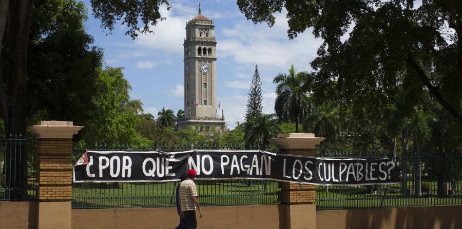 Dos estudiantes caminan frente a un letrero de protesta que fue colocado en los portones de la  UPR en Río Piedras durante el proceso huelgario que impulsaron los universitarios el pasado año. (GFR Media) (horizontal-x3)