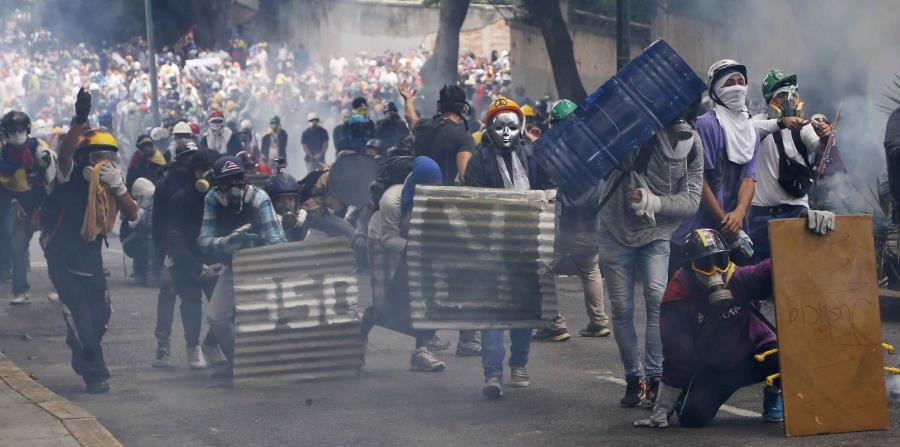 Centenares de opositores bloquearon algunas vías del este y oeste de Caracas con barricadas de basura, árboles, escombros, metales retorcidos y hasta banderas venezolanas de varios metros de largo que fueron colgadas entre los postes de luz. (horizontal-x3)