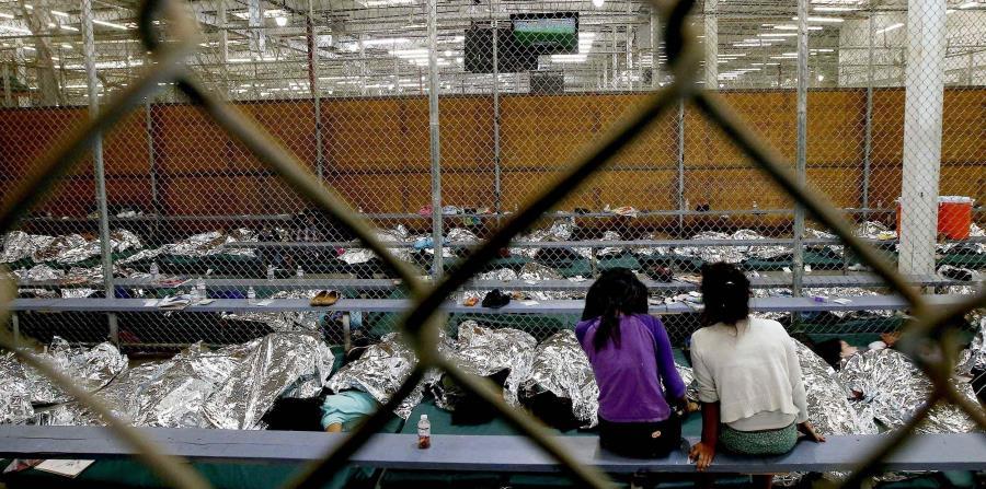 dos jóvenes ven un partido del Mundial de fútbol en un televisor desde la zona en la que están recluidas con cientos de niños migrantes centroamericanos en un centro de la patrulla fronteriza de Estados Unidos en Nogales, Arizona. (AP (horizontal-x3)