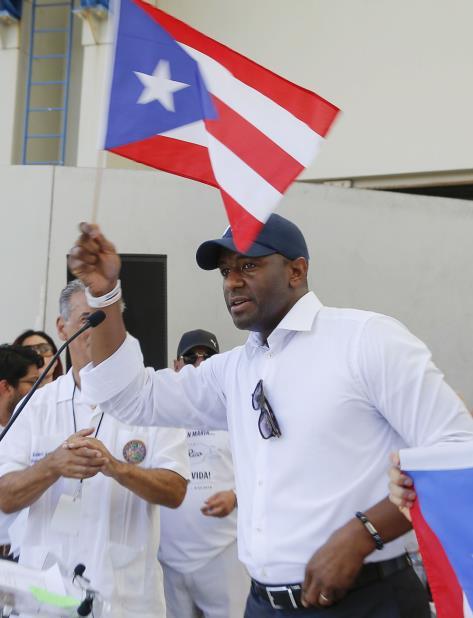 El alcalde de Tallahassee y candidato a la gobernación de Florida por el Partido Demócrata, Andre Gillum aguanta una bandera de Puerto Rico durante un mitin en West Palm Beach, en Florida., el 22 de septiembre de 2018, a un año del paso del huracán María. (vertical-x1)