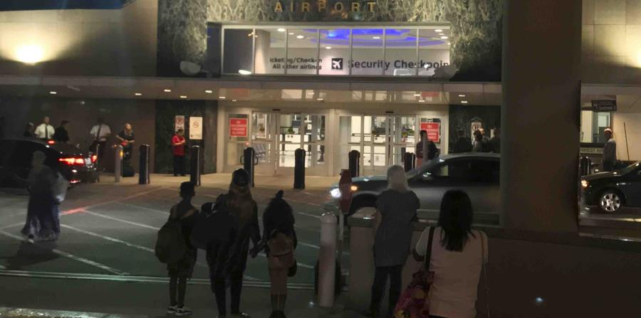 Unas personas esperan afuera del Aeropuerto William P. Hobby de Houston debido a que una granada de juguete en el bolso de un pasajero provocó el cierre de un punto de control, el jueves 6 de junio de 2018. (horizontal-x3)