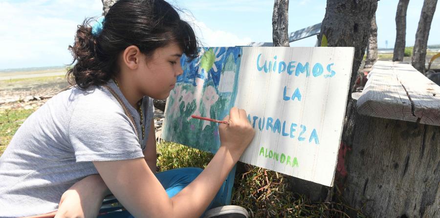 Alondra Caraballo Rodríguez disfruta de pintar rótulos en la Playa de Guayanilla, con mensajes de concienciación ambiental. (horizontal-x3)