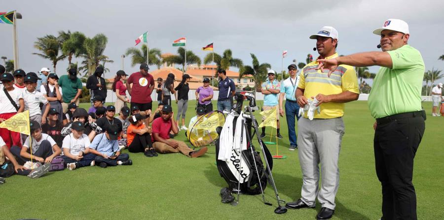 Iván Rodríguez (der.) y Rafael Campos (centro) conversan con los niños que asistieron a la clínica de golf. (horizontal-x3)