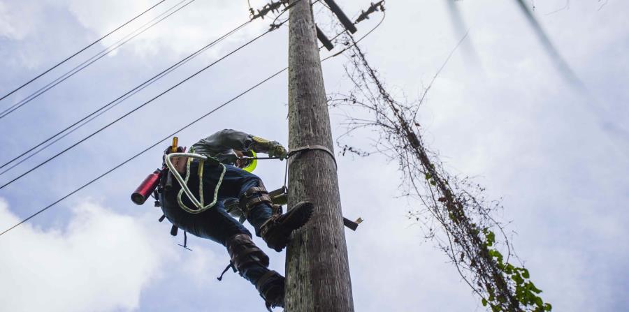 Un trabajador de la AEE sube a un poste a hacer reparaciones del sistema eléctrico. (horizontal-x3)