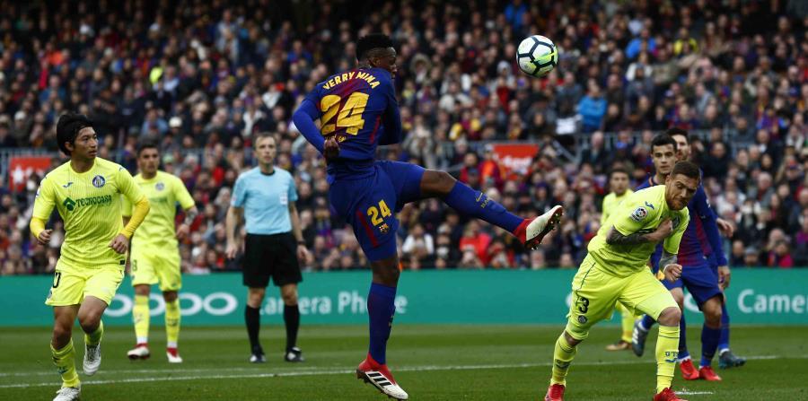Yerry Mina, al centro, patea la bola en el partido contra el Getafe en el Camp Nou, en Barcelona. (AP) (horizontal-x3)