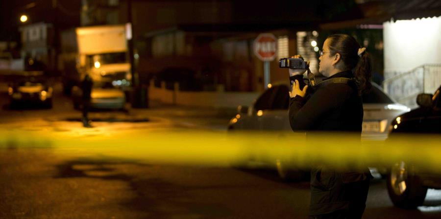 Una agente graba una escena de un crimen. (GFR Media) (horizontal-x3)