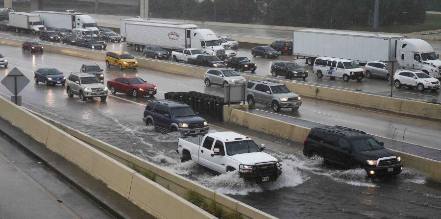 Los vehículos  transitan por las inundaciones en una carretera de la ciudad de Houston. (AP) (horizontal-x3)