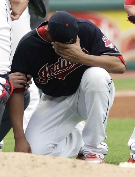 El abridor venezolano Carlos Carrasco, de los Indios de Cleveland, se duele tras recibir un pelotazo en el brazo derecho durante un batazo en el partido ante los Mellizos de Minnesota, el sábado 16 de junio de 2018, en Cleveland. (AP) (vertical-x1)