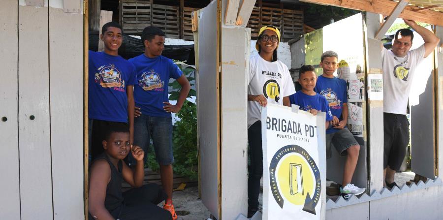 """Jesús """"Bubu"""" Negrón y los niños de Puerta de Tierra celebran la gesta de crear una parada de guagua que tiene por techo un árbol de almendro y que se ajusta a las necesidades de la comunidad. (horizontal-x3)"""