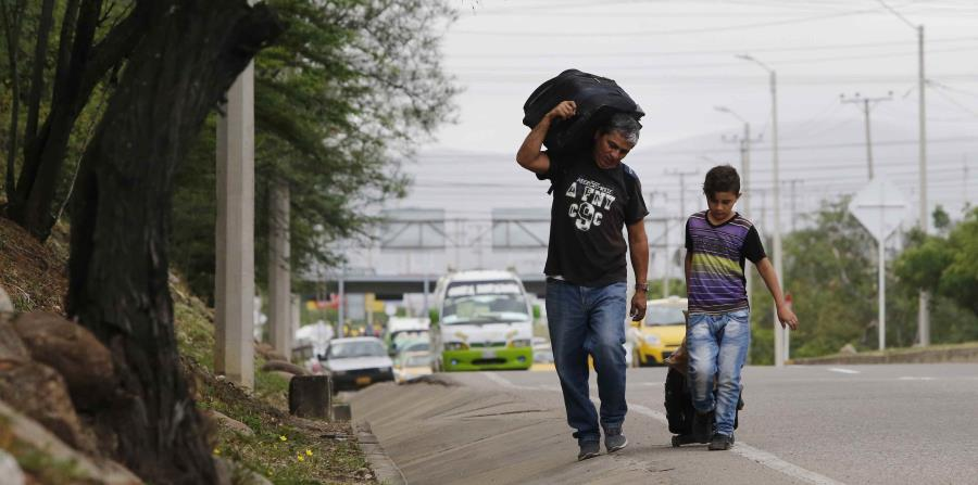 el venezolano Darwin Zapata camina acompañado por su hijo de 12 años por la carretera en Cúcuta, Colombia, mientras se dirigen a Perú. (horizontal-x3)