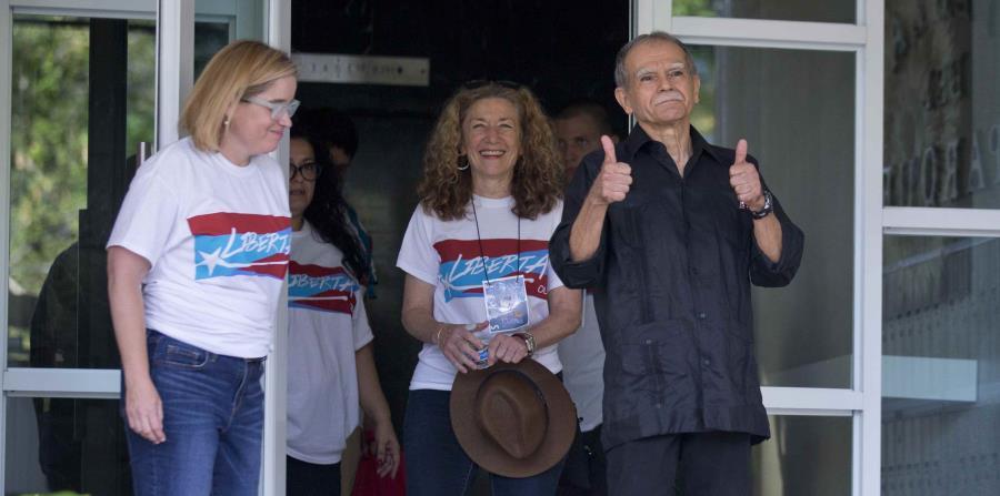 Escoltado por la alcaldesa sanjuanera, López realiza una señal de que todo estará bien. (horizontal-x3)