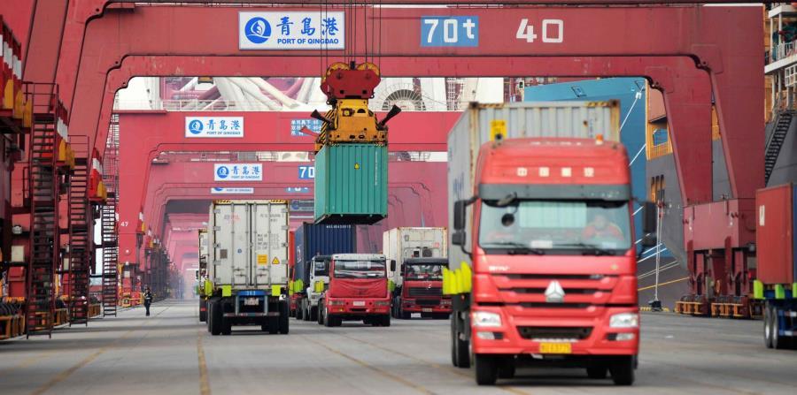 Varios camiones mientras transportan contenedores en un puerto en Qingdao, China (horizontal-x3)