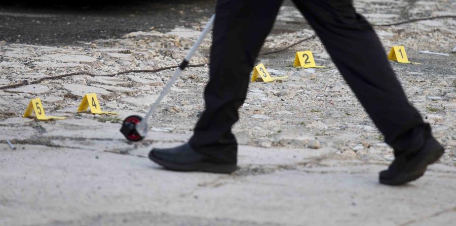 Un agente toma medidas en una escena de un asesinato. (GFR Media) (horizontal-x3)