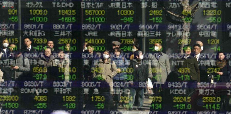 La imagen de varias personas se refleja en el indicador accionario electrónico de una firma de valores en Tokio (horizontal-x3)