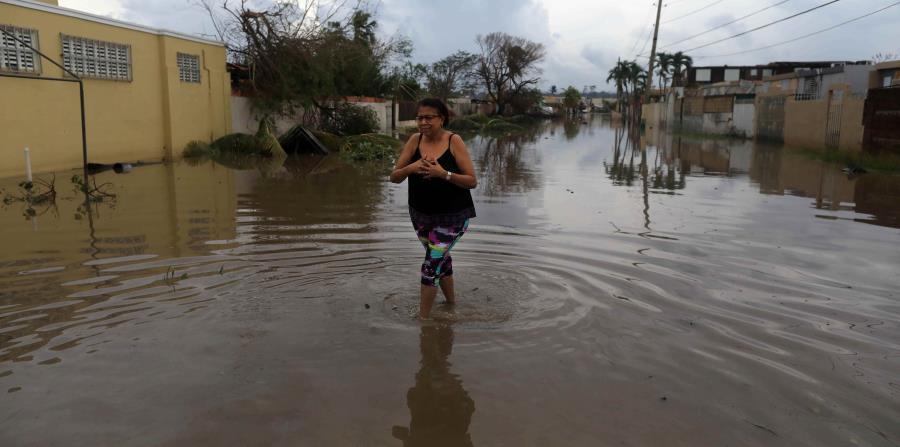 Una mujer camina por una de las calles que se inundaron tras el paso del huracán María en la urbanización Levittown, en Toa Baja. (GFR Media) (horizontal-x3)