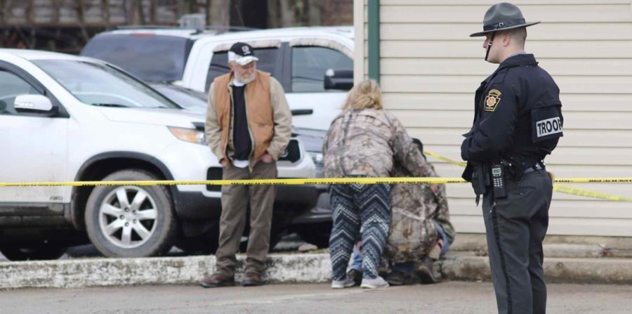 Un policía monta guardia mientras otras personas se consuelan cerca del lugar de un tiroteo en un lavado de autos de Mecrof, Pensilvania. (Michael Palm / Herald-Standard vía AP) (horizontal-x3)