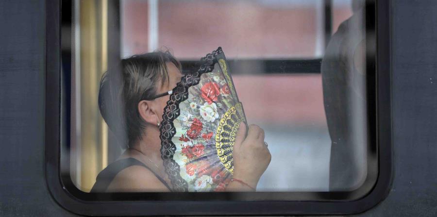 Una mujer usa un abanico para refrescarse mientras viaje en un tram en Bucarest, Rumania. (horizontal-x3)