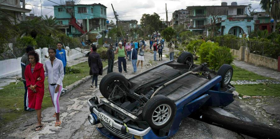 Ciudadanos cubanos caminan junto a un automóvil que fue volcado por los fuertes vientos del tornado que azotó a La Habana. (AP / Ramón Espinosa) (horizontal-x3)