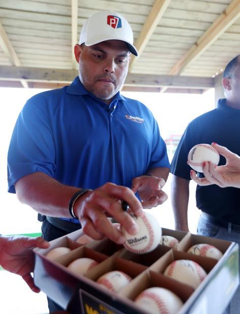 El exreceptor Iván Rodríguez, miembro de la Comisión de Igualdad, firma bolas de béisbol. (vertical-x1)