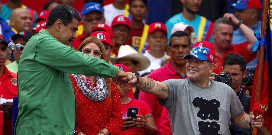 El presidente venezolano, Nicolás Maduro (i), saluda junto a la primera dama, Cilia Flores (c), y al exfutbolista argentino, Diego Maradona (d), durante su evento de cierre de campaña (horizontal-x3)