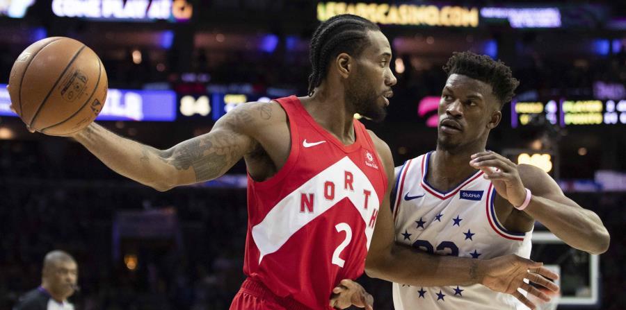 El alero Kawhi Leonard intenta pasar el balón ante la defensa de Jimmy Butler, de los 76ers de Filadelfia. (AP / Chris Szagola) (horizontal-x3)