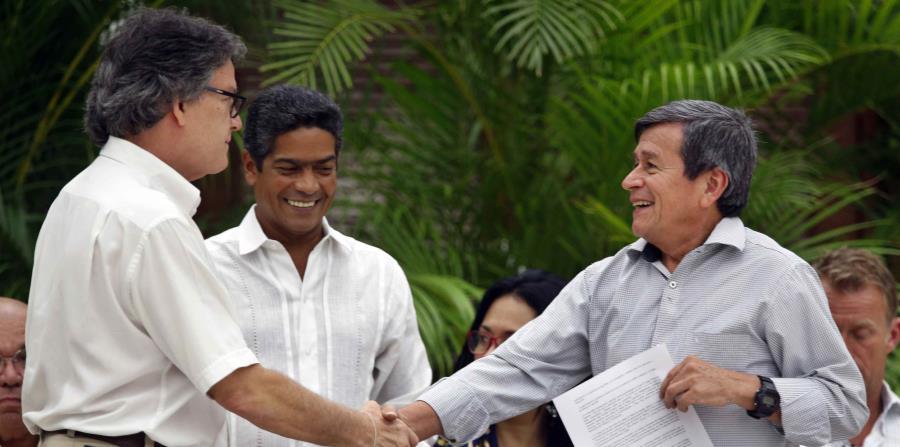 El jefe negociador del gobierno colombiano, Gustavo Bell (izq.), estrecha la mano del comandante del ELN Israel Ramírez Pineda (der.), alias Pablo Beltrán. (EFE / Ernesto Mastrascusa) (horizontal-x3)