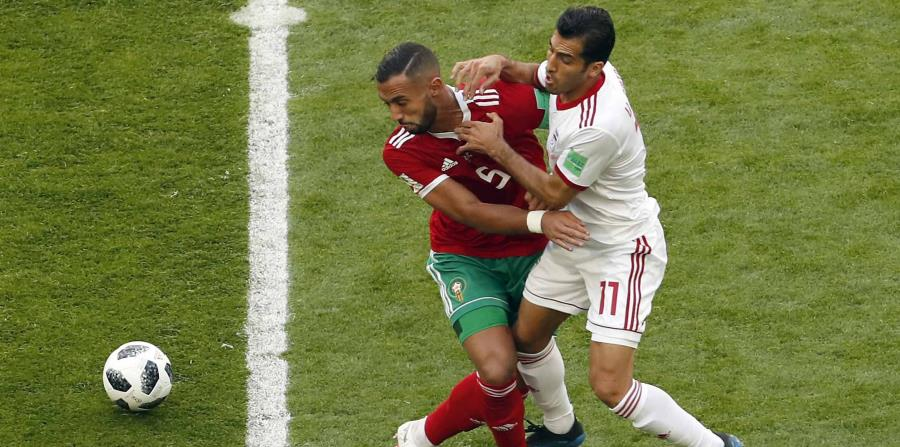 Mehdi Benatia, de la selección de Marruecos, forcejea con Vahid Amiri, de Irán (horizontal-x3)