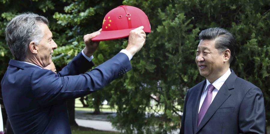 El mandatario chino Xi Jinping recibe un casco de polo decorado con la bandera de China de parte del presidente argentino Mauricio Macri. (AP) (horizontal-x3)