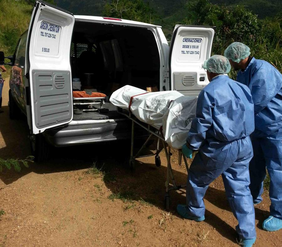 Personal del Negociado de Ciencias Forense introduce un cadáver en uno de sus vehículos. (GFR Media) (semisquare-x3)