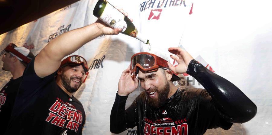 El receptor boricua René Rivera (izq.) derrama champaña sobre su compañero de equipo Ender Inciarte luego de capturar el banderín de la División del Este de la Liga Nacional. (AP / John Bazemore) (horizontal-x3)