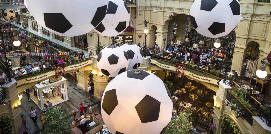 En esta imagen del viernes 29 de junio, turistas y aficionados del futbol caminan por el centro comercial GUM decorado con enormes balones de fútbol con motivo del Mundial en Moscú, Rusia. (AP) (horizontal-x3)