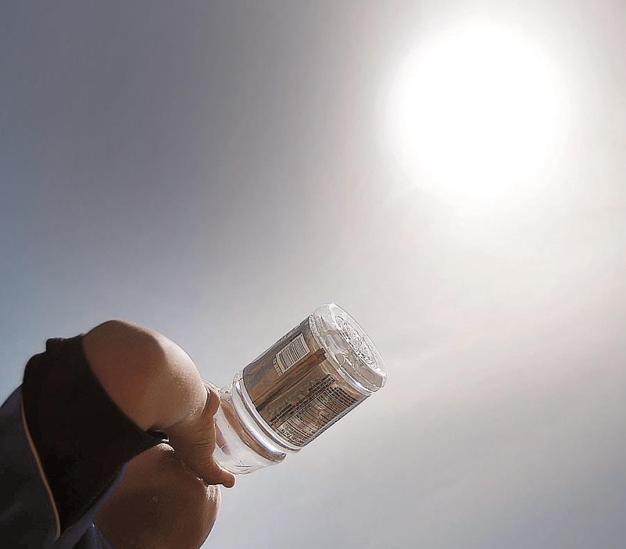 Un hombre bebe agua para aliviar el calor del día. (GFR Media) (semisquare-x3)