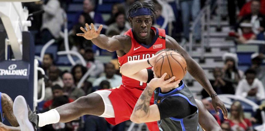 El jugador de los Pelicans, Jrue Holiday  defiende al novato de los Mavericks, Luka Doncic. (AP) (horizontal-x3)