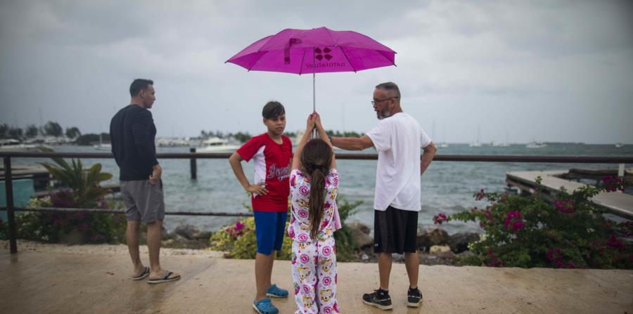 Una niña aguanta una sombrilla mientras observa el mar junto a otras personas. (GFR Media) (horizontal-x3)