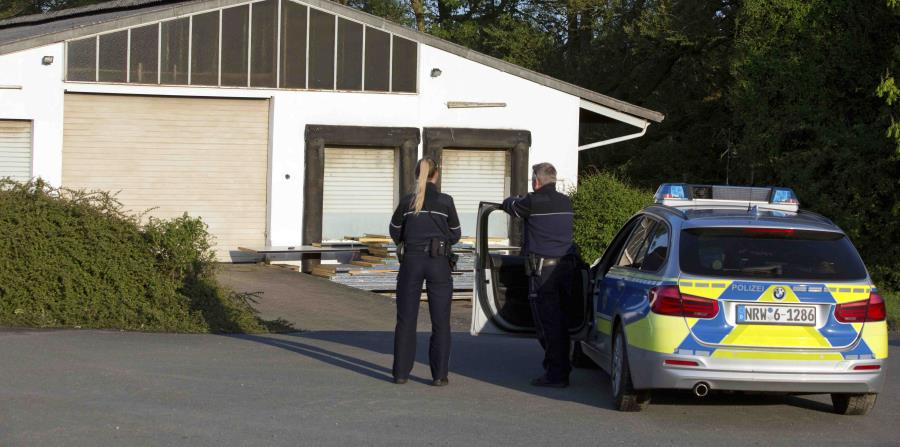 Dos agentes de policía de pie ante un almacén donde se encontraron sustancias peligrosas en la localidad de Preussisch Oldendorf, cerca de la ciudad de Bielefeld, Alemania. (Oliver Krato/dpa via AP) (horizontal-x3)