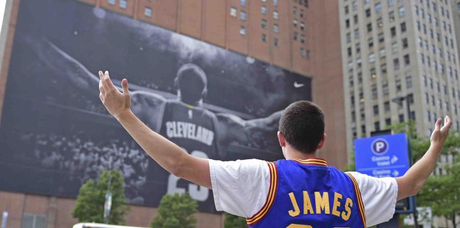 Un fanático de LeBron James se toma una foto junto al gigante afiche del astro de la NBA en Cleveland. (AP) (horizontal-x3)