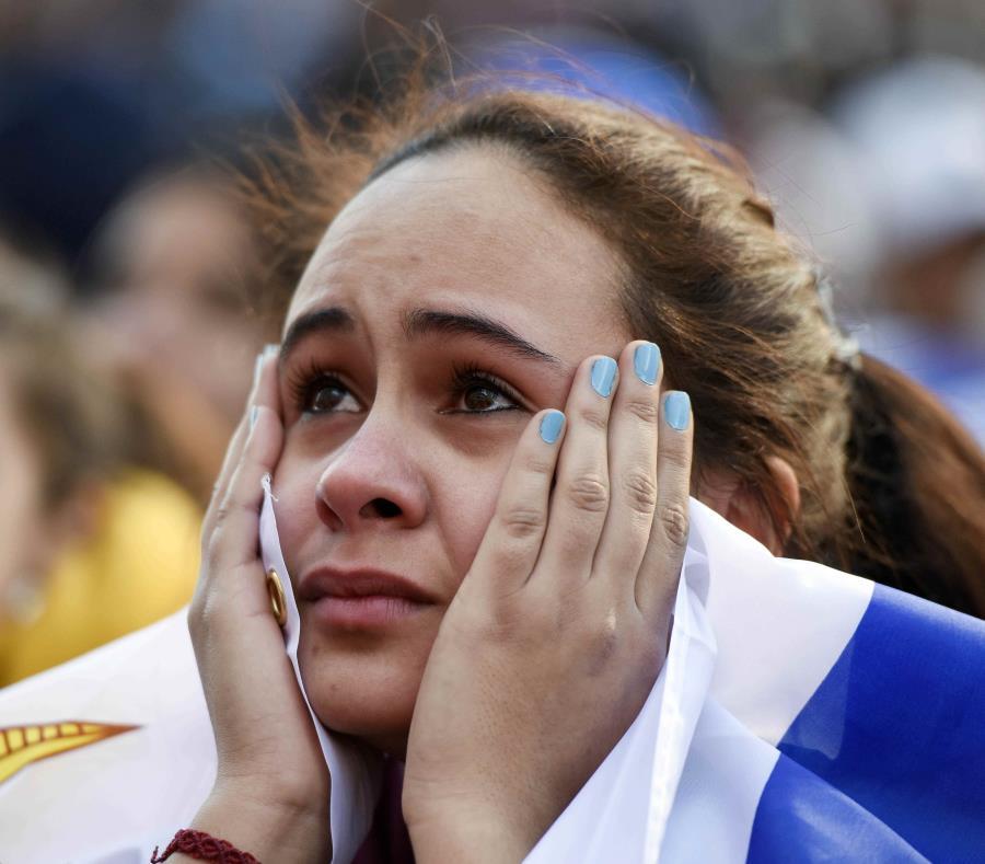 Una seguidora de la selección de Uruguay observa la transmisión del partido del Mundial entre Francia y Uruguay en el centro de Montevideo. (AP) (semisquare-x3)