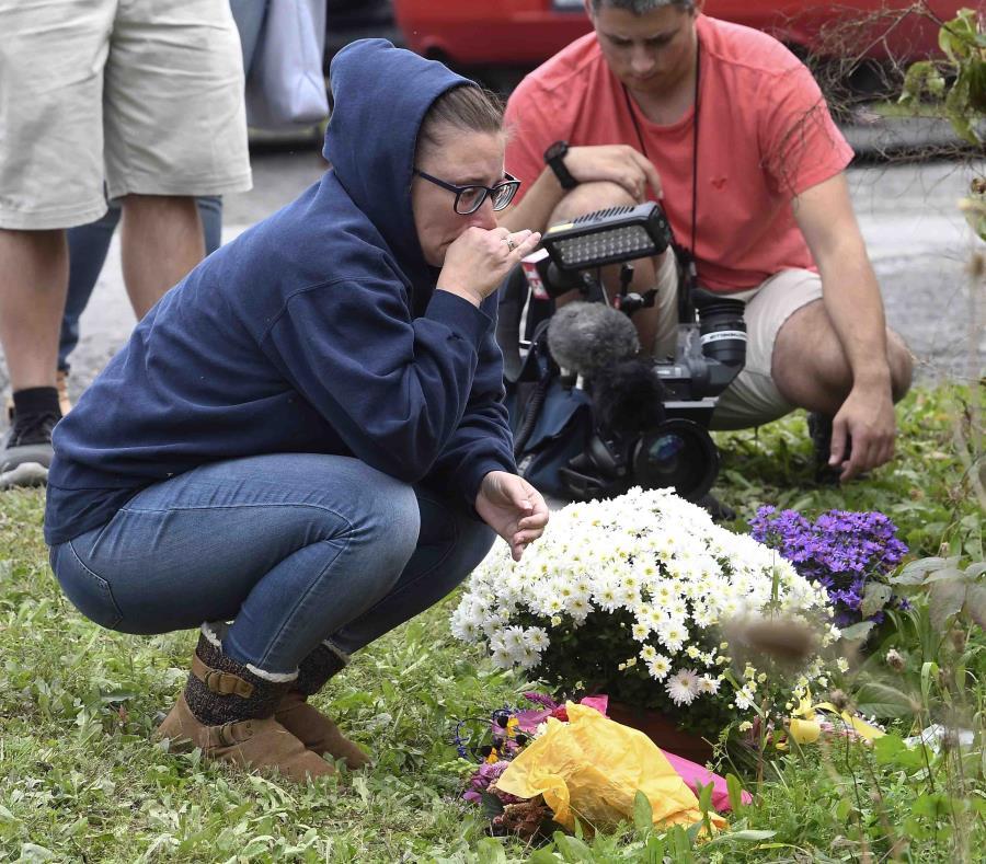 Una mujer aparece enfrente de un altar improvisado en el lugar donde el día previo chocó una limusina dejando 20 muertos, en Schoharie, Nueva York. (AP) (semisquare-x3)