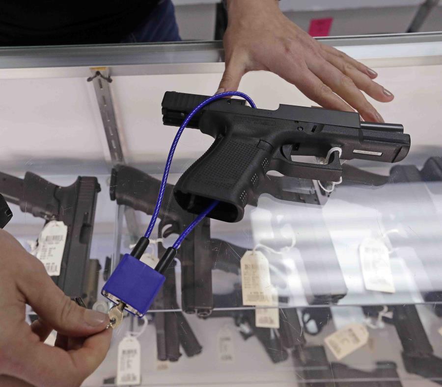 Un empleado de una armería muestra varias armas. (AP) (semisquare-x3)