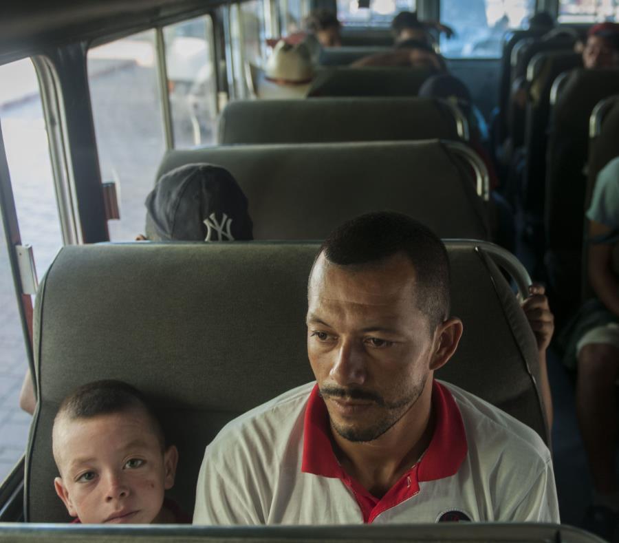 Migrantes hondureños aguardan en un autobús de la policía luego de que aceptaran voluntariamente regresar a su país, en Tecún Umán, Guatemala. (AP / Oliver de Ros) (semisquare-x3)