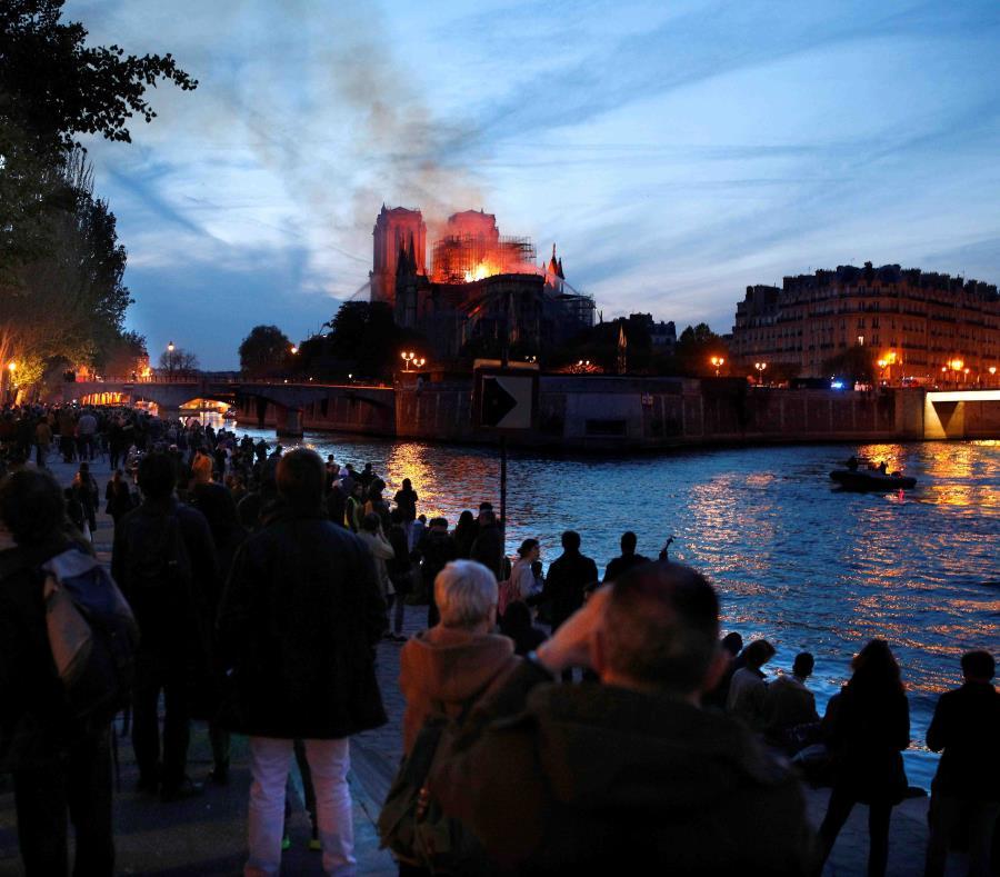 Decenas de personas en la orilla del río Sena observan la columna de humo y las llamas que consumen a la catedral de Notre Dame este lunes, en París.  (EFE) (semisquare-x3)